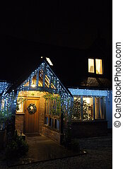 Coming home to festive lights - Exterior of English home lit...
