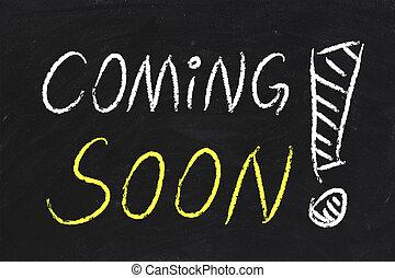 Coming Soon text is written by chalk on blackboard.