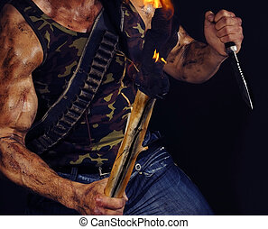 Commando - Body of muscular commando holding knife and torch