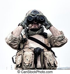 Special operations forces soldier, Navy SEAL scout in battle uniform and helmet, looking through binoculars, observing area, searching targets, monitoring enemy movements, directing artillery fire
