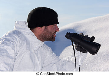Commandos in white camouflage looking through binoculars in the mountains on the white snow. Portrait in Profile