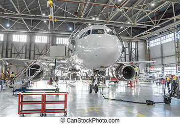 Commercial aircraft jet on maintenance of engine and fuselage check repair in airport hangar.