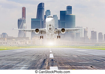 Commercial aircraft jetliner approaching for landing on runway, modern city on background.