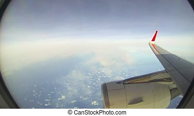 """""""Red wingtip and massive engine cowling of a commercial airliner, as seen through the passenger window, with multiple layers of sparse clouds below."""""""