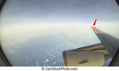 Red wingtip and massive engine cowling of a commercial airliner, as seen through the passenger window, with multiple layers of sparse clouds below.