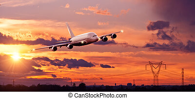 Commercial airplane flying above city in sunset ligt -...