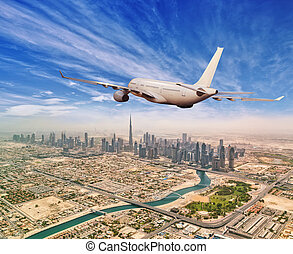Commercial airplane flying above Dubai city