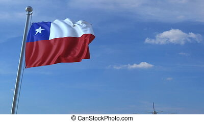 Commercial airplane flying above waving flag of Chile....