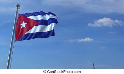 Commercial airplane flying above waving flag of Cuba. Cuban...