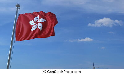 Commercial airplane flying above waving flag of Hong Kong....