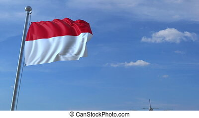 Commercial airplane flying above waving flag of Indonesia....