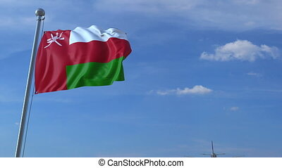 Commercial airplane flying above waving flag of Oman. Omani...
