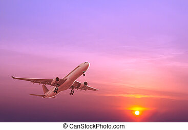 Commercial airplane flying at sunset