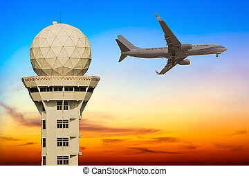 Commercial airplane flying over airport control tower at sunset