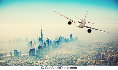 Commercial airplane flying over modern city