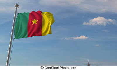 Commercial airplane flying over national flag of Cameroon....