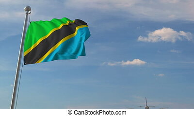 Commercial airplane flying over national flag of Tanzania....
