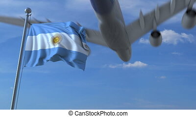 Commercial airplane landing behind waving Argentinian flag. ...