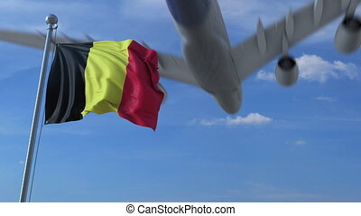 Commercial airplane landing behind waving Belgian flag. Travel to Belgium conceptual animation