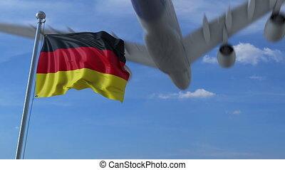 Commercial airplane landing behind waving German flag. ...