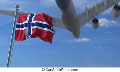 Commercial airplane landing behind waving Norwegian flag....