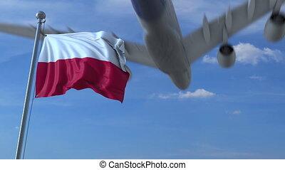 Commercial airplane landing behind waving Polish flag. ...