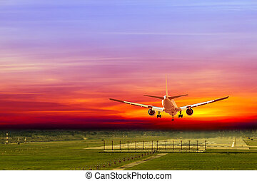 Commercial airplane landing on runway in airport at sunset