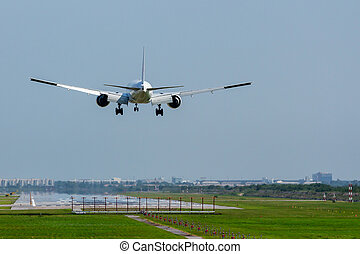 Commercial airplane landing on runway in airport