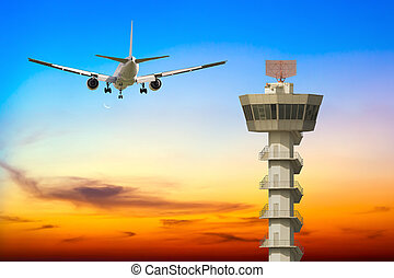 Commercial airplane take off over airport control tower at sunset