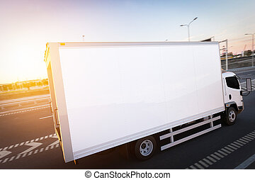 Commercial cargo delivery truck with blank white trailer driving on highway.