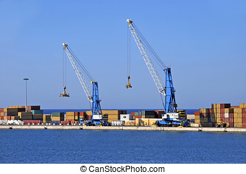 Commercial harbor - Two cranes and some containers at a...