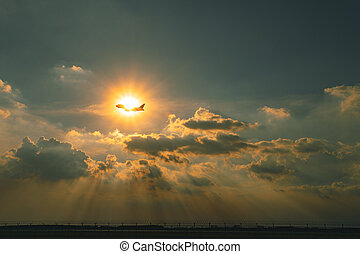 commercial plane flying over sky against beautiful sun ray through cloudscape