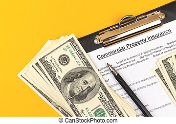 Commercial property insurance form. Contract and agreement of real property. Clipboard with pen, dollars and pen on a business desktop. Top view photo