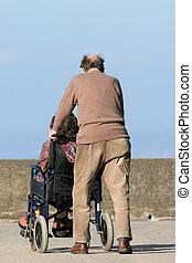 Commitment - Rear view of an elderly man pushing an elderly ...