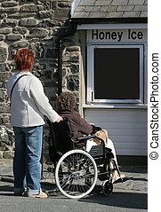 Committed Helper - Elderly female in a wheelchair being...