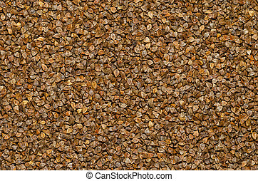 Common buckwheat seeds with husks, surface and background. Gluten-free pseudocereal with grain-like seeds, used as a cover crop. Fagopyrum esculentum. Food photo, top view, from above.