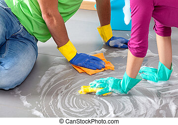 Common cleaning - Happy couple cleaning floor together in...