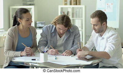 Common Goal - Three adult friends drawing at the desk