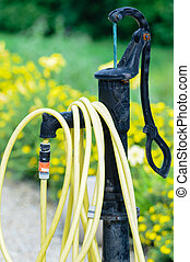 common home garden hose coiled up and hanging on a fountain