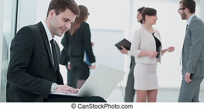 communication concept:businessman working with laptop on the kne