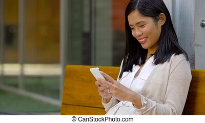 asian woman using smartphone sitting on bench -...
