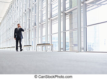 Low angle shot of a corporate executive walking along a modern corridor talking on his mobile phone