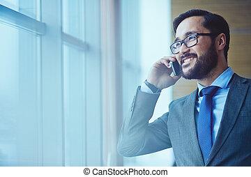 Communication - Smiling businessman in eyeglasses talking on...