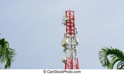 Communication tower, cellphone tower in the jungle in the mountains. Aerial view: satellite, cellphone tower, on a mountain. View of a tropical island with palm trees.