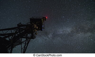 Communication tower  in starry night time lapse. Moving stars sky with milky way galaxy