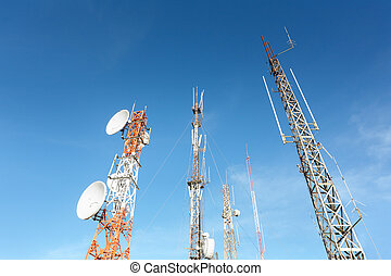 Several communication towers in the morning, against clear blue sky