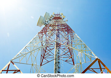 communications tower showing sun flare with antennas against blue sky