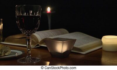 A tracking shot of a candle lit communion setting with wine, bread and the Bible.