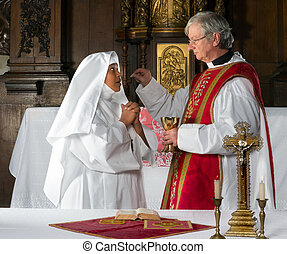 Communion and nun - Catholic priest giving holy communion to...
