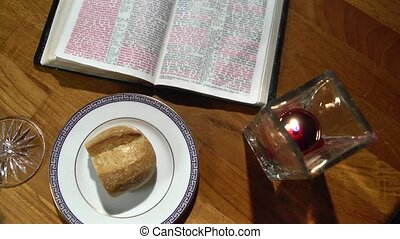 Pan of a candle lit communion setup with bread, wine and the Bible.